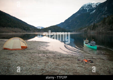 Rear view of young couple canoeing on lake against mountains and clear sky
