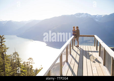 Couple looking face to face against mountains at observation point during sunny day - Stock Photo