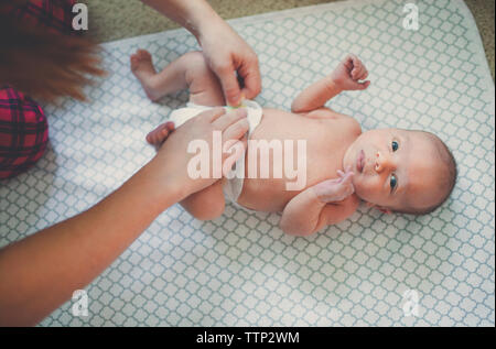 Cropped image of mother wearing diaper for baby boy lying on blanket - Stock Photo