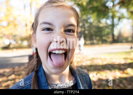 Close-up portrait of girl sticking out tongue while standing at park - Stock Photo