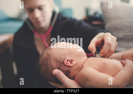 Female doctor examining newborn baby boy in hospital - Stock Photo