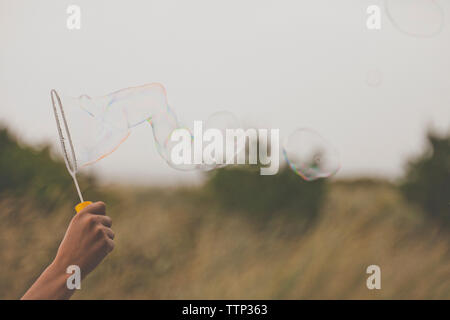 Cropped hand of man holding bubble wand on field - Stock Photo