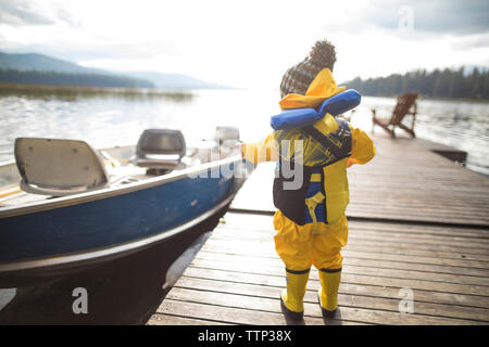 Rear view of baby boy wearing raincoat and life jacket while standing on wooden pier over lake - Stock Photo