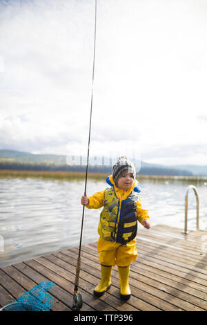 Baby boy wearing raincoat and life jacket while holding fishing rod on wooden pier over lake - Stock Photo