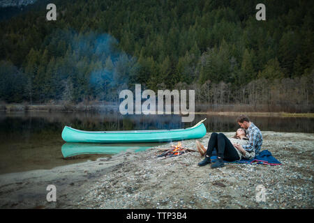 Full length of couple resting by campfire on lakeshore at Silver Lake Provincial Park