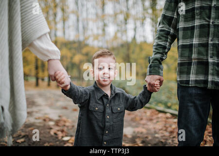 Portrait of cute smiling son holding parents hands while standing in forest during autumn