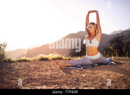 Woman doing splits on field against clear sky - Stock Photo