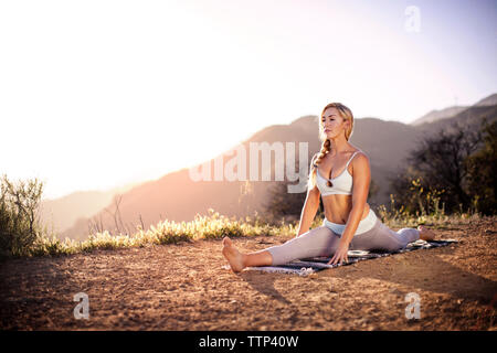 Woman doing splits on field against sky - Stock Photo