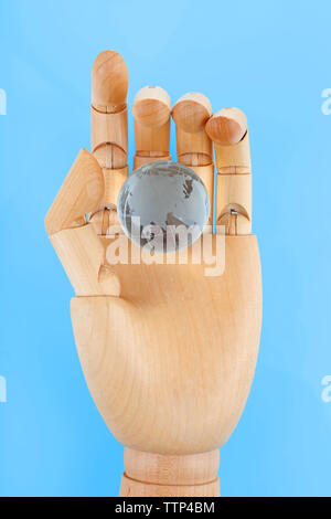 Wooden hand holding small glass globe on white background - Stock Photo