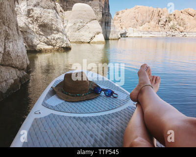 Low section of woman with hat and sunglasses sitting on paddleboard in lake against rock formations - Stock Photo