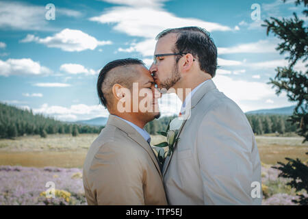 Man kissing boyfriend on forehead while standing against cloudy sky - Stock Photo