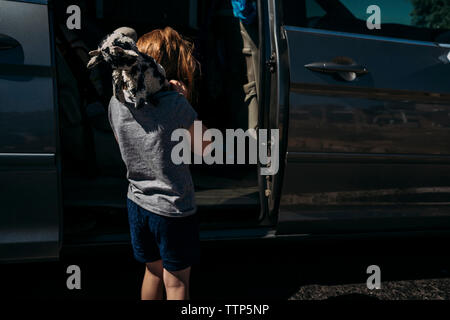 Rear view of girl carrying stuffed toy on shoulders while standing by car door during sunny day - Stock Photo