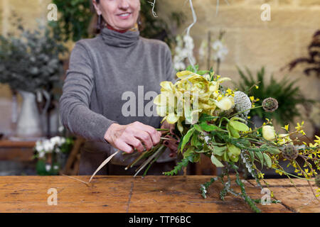 Cropped image of a senior woman arranging flowers at flower shop desk - Stock Photo