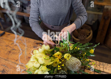 Cropped image of unrecognisable woman arranging flowers at flower shop - Stock Photo