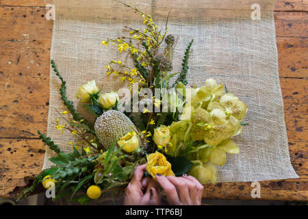 Cropped image of woman hands arranging bouquet of flowers at desk - Stock Photo