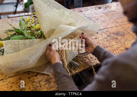Cropped image of senior woman arranging bouquet flowers at desk - Stock Photo
