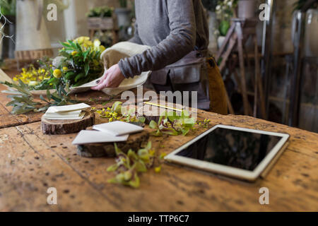 Cropped image of unrecognisable woman arranging bouquet of flowers - Stock Photo