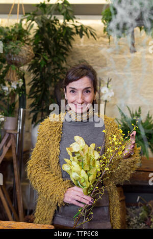 Portrait of cheerful senior woman holding yellow flowers at flowershop - Stock Photo