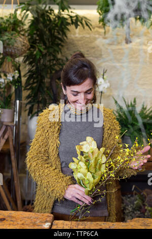 Portrait of cheerful woman holding yellow flowers at slower shop - Stock Photo