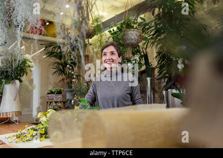 Portrait of cheerful senior woman behind flower shop desk - Stock Photo