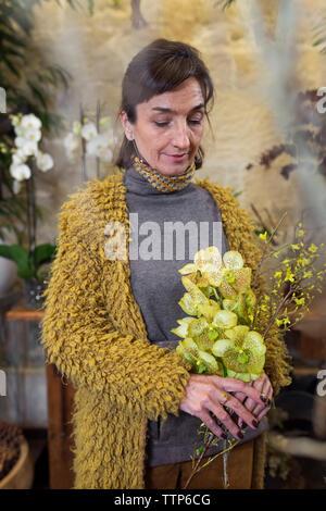 Close up portrait of senior woman holding yellow flowers - Stock Photo