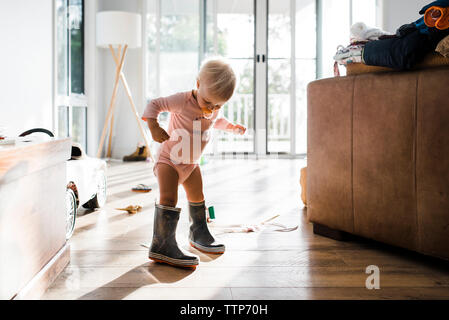 Toddler wearing rubber boots while sucking pacifier at home - Stock Photo