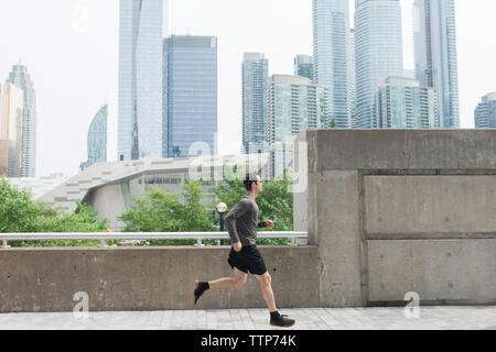 Side view of man running on footbridge against modern buildings in city