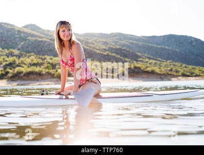 Smiling woman looking away while sitting on paddleboard in Bartlett Lake - Stock Photo