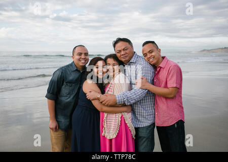 Portrait of happy family standing on shore at beach against sky - Stock Photo