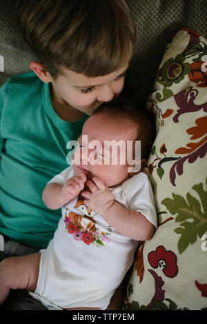 High angle view of brother kissing sister while lying on bed at home - Stock Photo