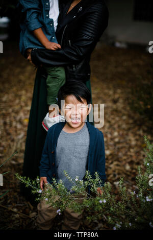Baby boy crying while mother carrying son on grassy field at Balboa Park - Stock Photo