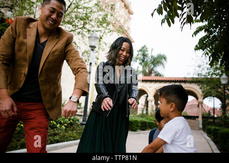 Happy parents dancing with sons while standing on footpath against sky at Balboa Park - Stock Photo