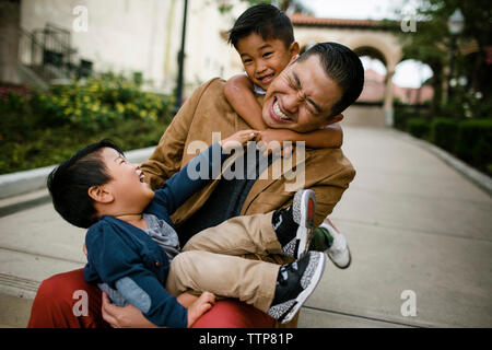 Happy father playing with sons while sitting on steps at Balboa Park - Stock Photo
