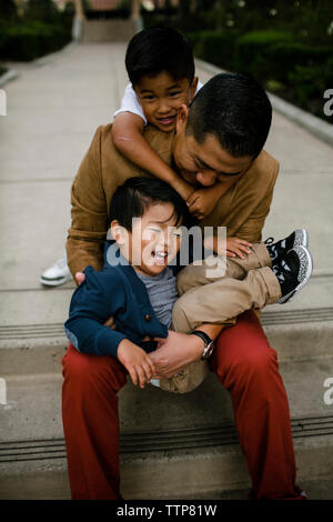 High angle view of happy father playing with sons while sitting on steps at Balboa Park - Stock Photo