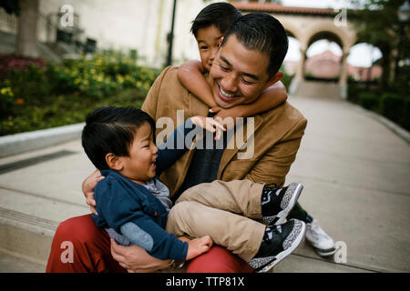 Happy father playing with sons while sitting on steps in Balboa Park - Stock Photo