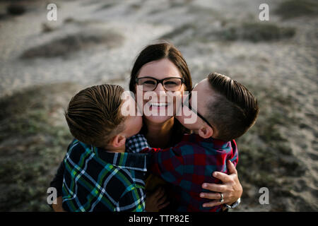 High angle portrait of happy mother being kissed by cute sons at beach during sunset