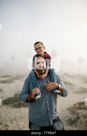 Portrait of father carrying cute son on shoulders while standing at beach against sky during foggy weather - Stock Photo