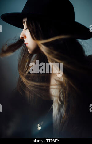 Young woman tossing hair against blue background - Stock Photo