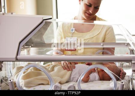Nurse touching baby girl lying in incubator at hospital