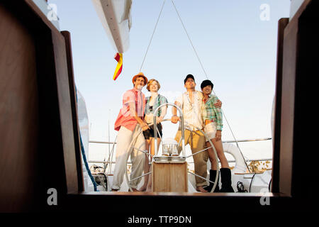 Happy couples standing by steering wheel on nautical vessel - Stock Photo