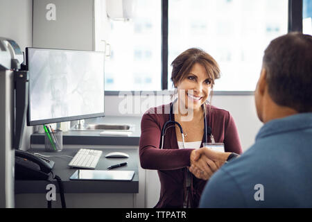 Happy female doctor shaking hands with male patient in clinic - Stock Photo