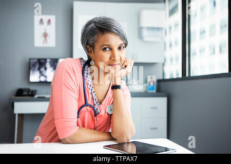 Portrait of confident female doctor leaning on desk in clinic - Stock Photo
