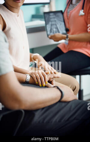 Midsection of daughter consoling father while sitting with female doctor in clinic - Stock Photo