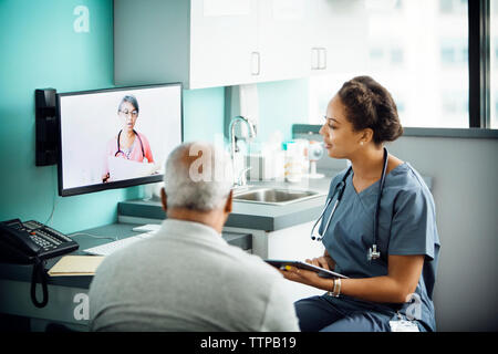 Female doctor discussing with female colleague on conference call while sitting with patient in clinic - Stock Photo