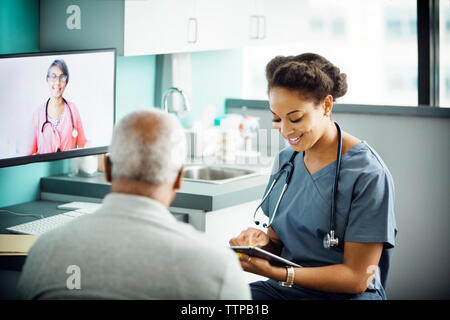 Happy female doctor using tablet computer while sitting with patient in clinic - Stock Photo