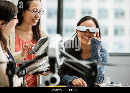 Female student wearing virtual reality glasses while teacher using tablet computer in classroom - Stock Photo