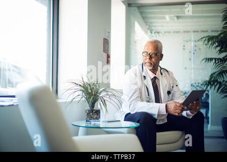 Doctor looking away while sitting with tablet computer on sofa in hospital - Stock Photo