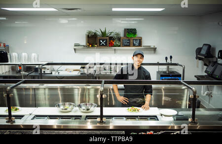 Portrait smiling chef standing in commercial kitchen - Stock Photo
