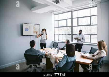 Businesswoman explaining data to colleagues in meeting at board room - Stock Photo