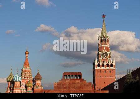 View to the Kremlin, St. Basil's Cathedral and Lenin mausoleum on Red Square in Moscow. Spasskaya tower against the blue sky with clouds